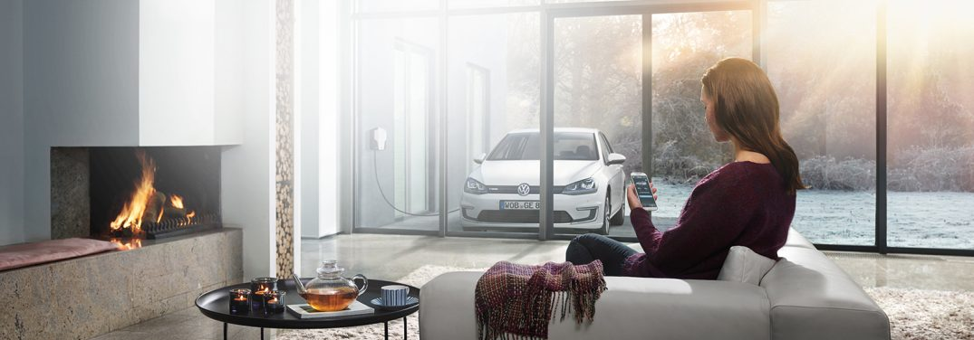 A woman remote starts her Volkswagen vehicle from the comfort of her ultra-modern living room.