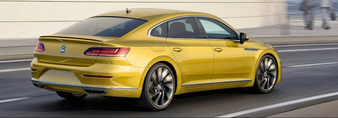 Yellow 2019 Volkswagen Arteon cruising up a highway with its beautiful wheels prominently displayed.
