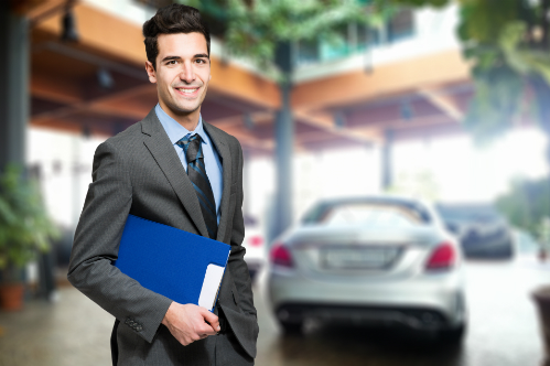 A smiling salesman holds a blue folder as he stands in front of a car.