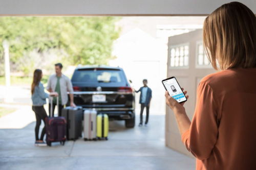 Woman using car-net on phone while family waits by VW car for her