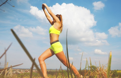 woman in yellow sports bra and shorts stretching in grass field
