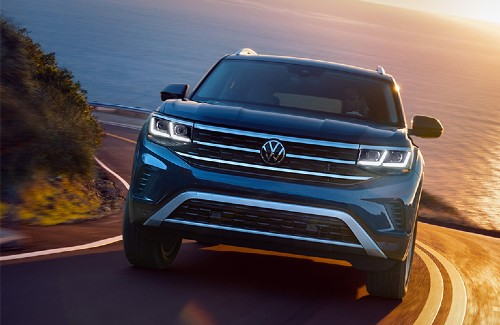 2021 VW Atlas exterior front driving on uphill curvy road sun setting background