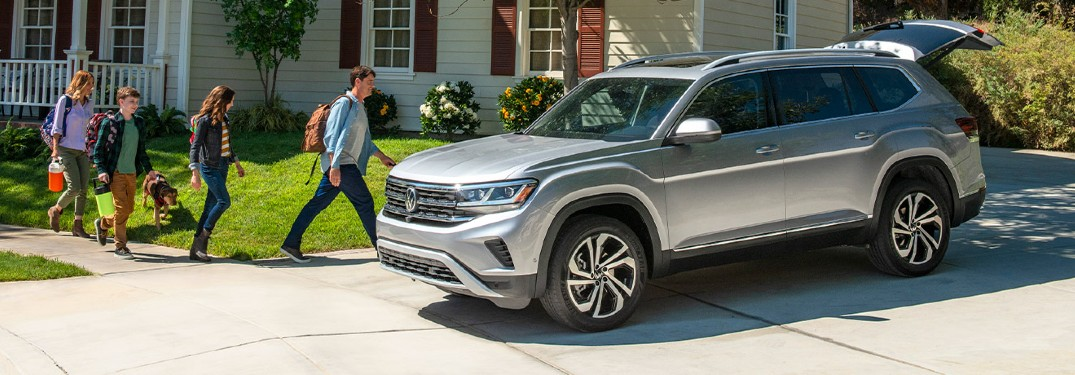 2021 VW Atlas grey exterior driver side front parked with tailgate open family walking toward with bags