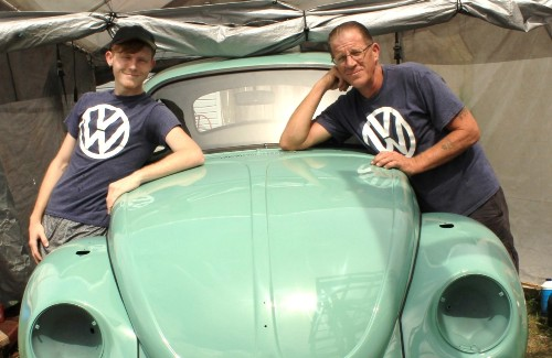 father and son leaning against mint green vw beetle