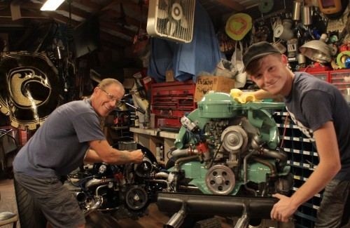 father and son standing in garage in front of mint green engine