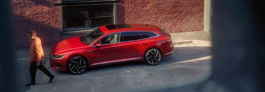looking out second story at man walking away from red vw arteon shooting brake
