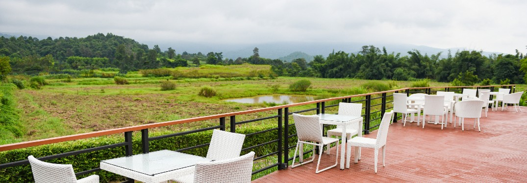 white tables and chairs on patio in countryside