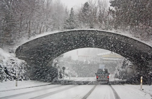 white vehicle driving under bridge during snowstorm