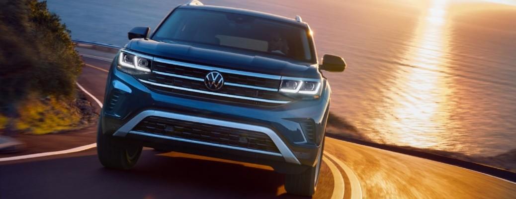 2021 Volkswagen Atlas driving down road near body of water.