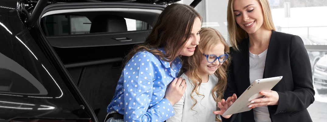 A stock photo of a sales person helping a family pick out a new crossover SUV.
