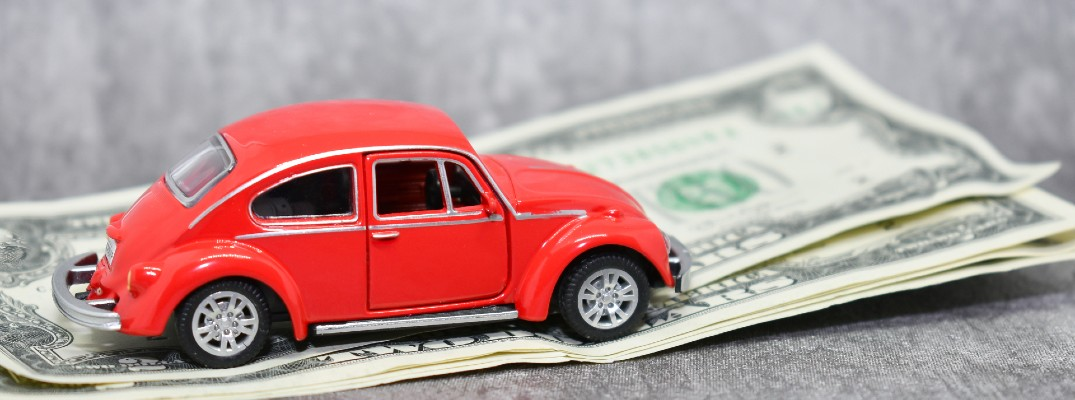 A stock photo of a toy VW Beetle on a few dollar bills.