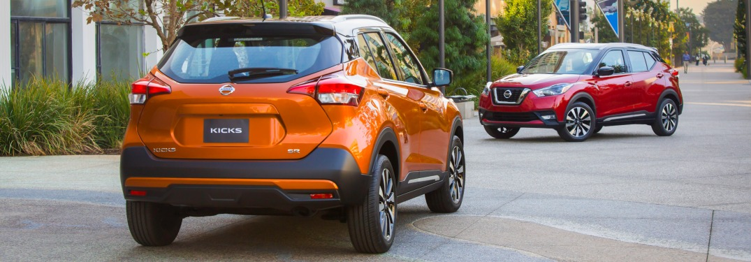 2018 Nissan Kicks orange back view with red model in the background