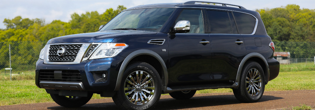 front and side view of blue 2018 nissan armada against green trees and grass