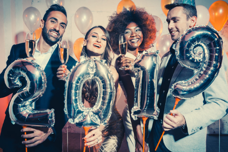 group of young people holding champagne with balloons spelling 2019