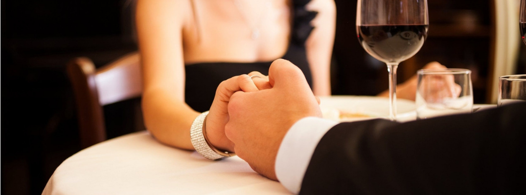 couple at fine dining restaurant holding hands