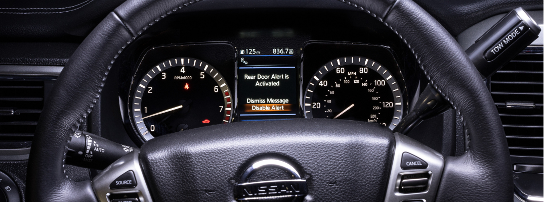 close up of 2019 nissan titan steering wheel and dashboard with rear door alert system