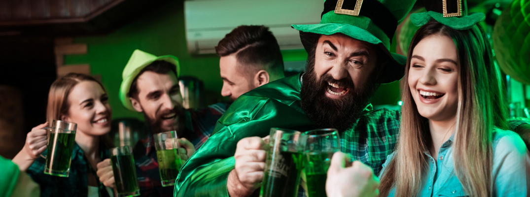 group of young people at bar wearing leprechaun costumes drinking green beer
