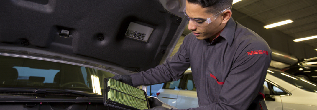nissan service technician examining air filter of car