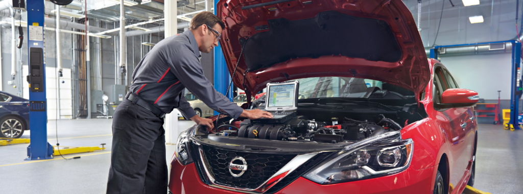 nissan service technician examining engine underneath hood of nissan car in garage