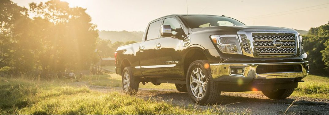 A 2019 Nissan Titan, parked in a green field with a forest backdrop, seems bathed in the glow of light from heaven.