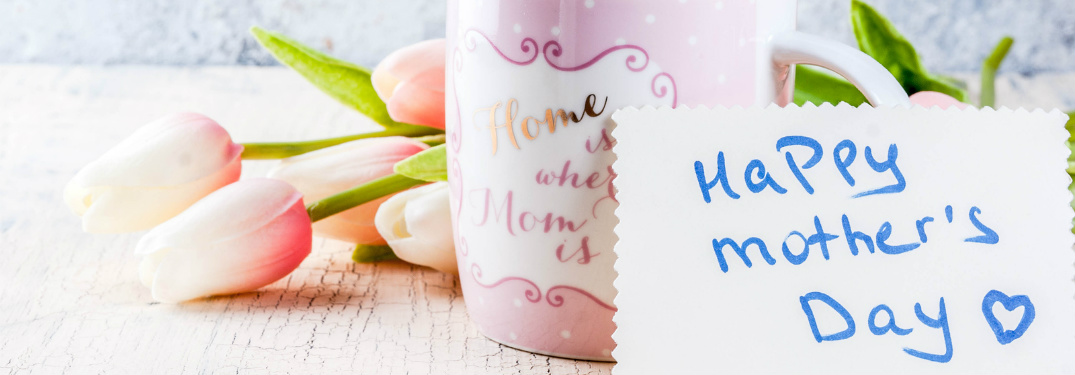 "A pink mug and some tulips sit on a table, fronted by a card that says ""Happy Mother's Day [heart]"" in blue ink."