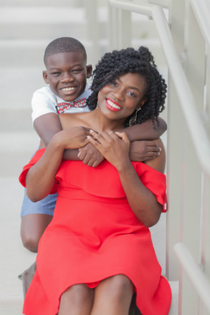 A woman in a red dress sits on some stairs and is hugged from behind by her son. Both smile.