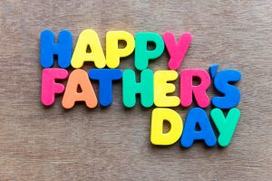 Child's toy letters spelling Happy Fathers Day over wooden background