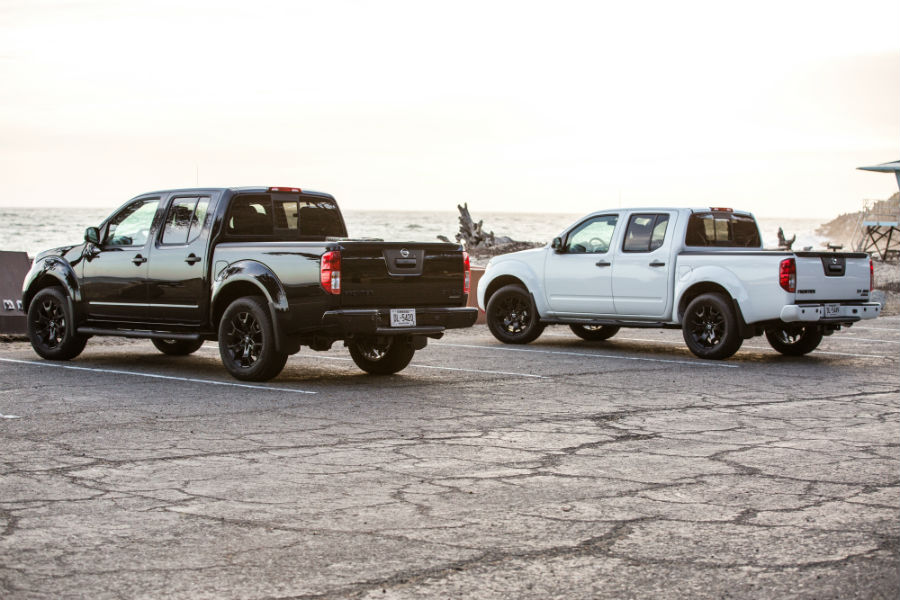 A photo of two Nissan Frontier models parked by the beach.