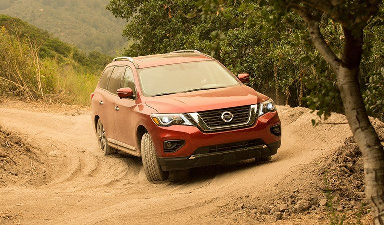 A front-end photo of the Nissan Pathfinder on a dirt road.