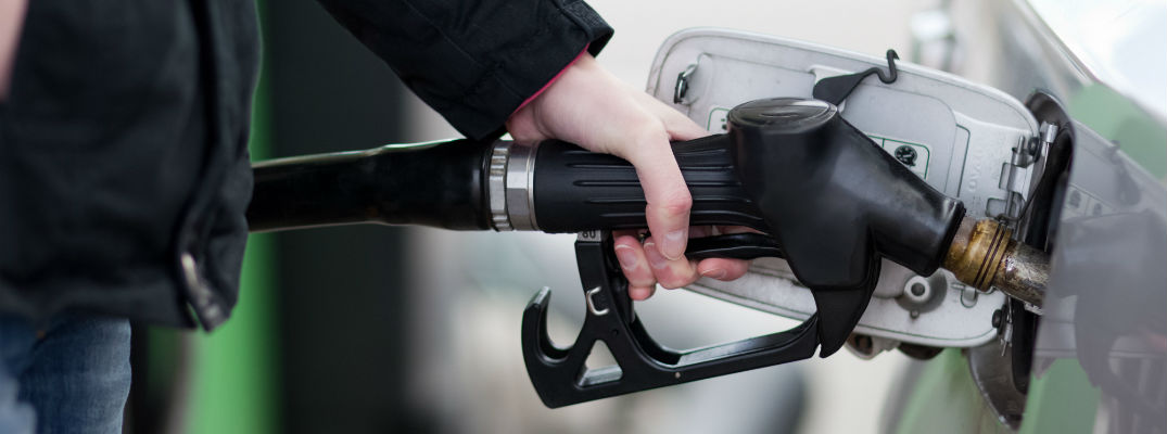 A stock photo of a person filling up a car with gas.