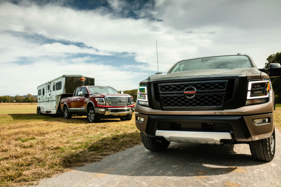 A photo of the two 2020 Nissan Titan XD models in a field.