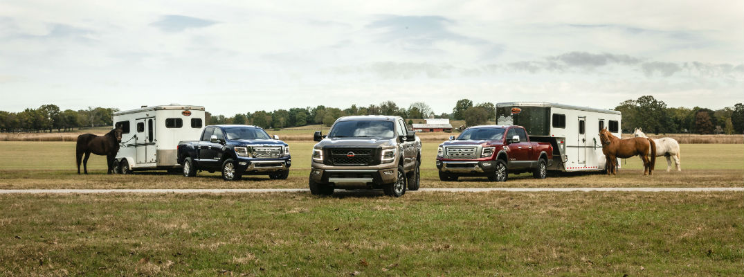 A photo of three 2020 Nissan Titan XD models with trailers in a field.