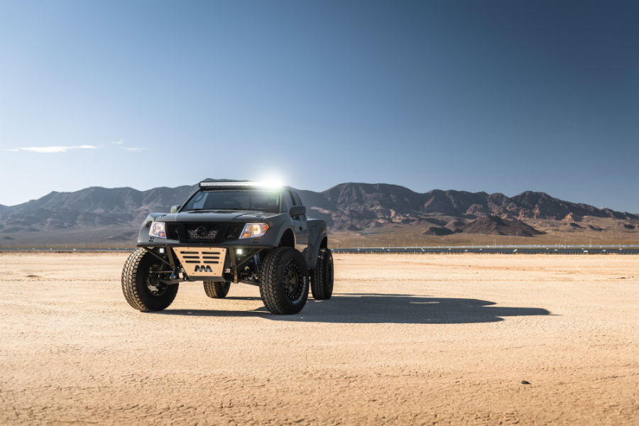A front-end photo of the Nissan Frontier Desert Runner with its top light bar turned on.