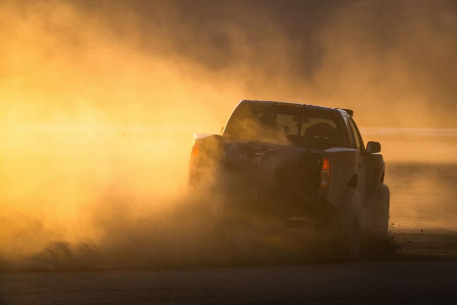 A rear photo of the Nissan Frontier Desert Runner kicking up dust in the desert.