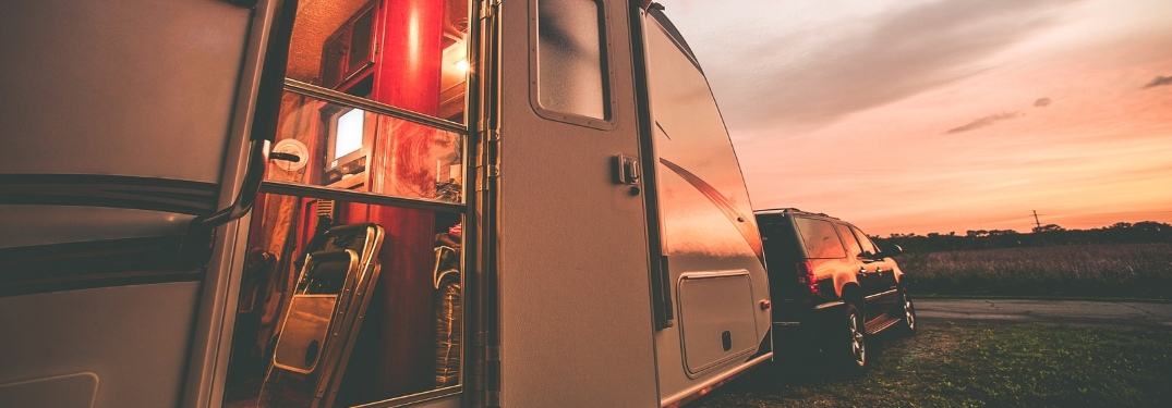 A camper hooked up to an SUV with a beautiful sunset in the distance