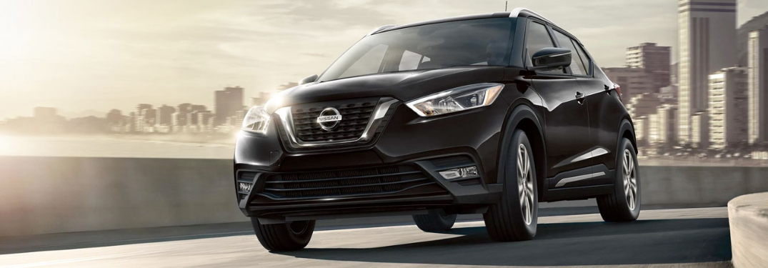 2020 Nissan Kicks going over a bridge with a big city in the background
