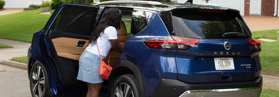 Woman getting items out of the back seat of the 2021 Nissan Rogue