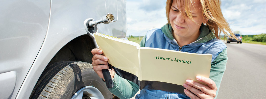 Woman reading the owner's manual of her vehicle