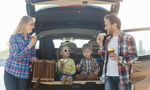 Family eating in the open cargo area of a vehicle