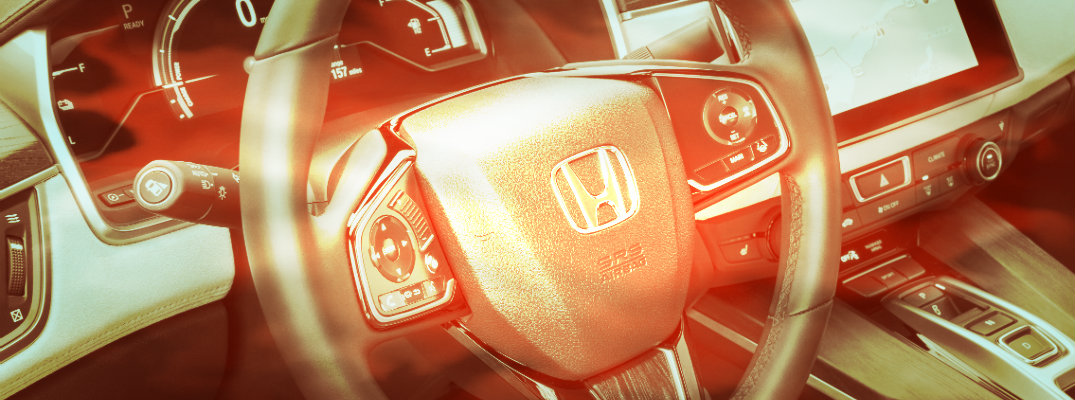 Orange-tinted photo of steering wheel in a Honda vehicle