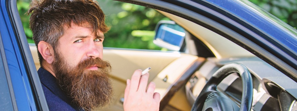 Bearded man smoking cigarette in front seat of vehicle
