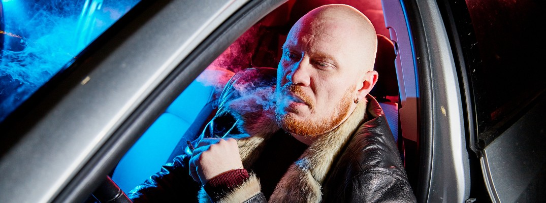 Bald man smoking inside vehicle