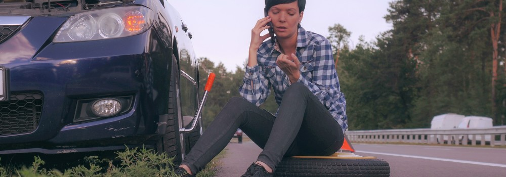 Young woman sitting on spare tire on side of road