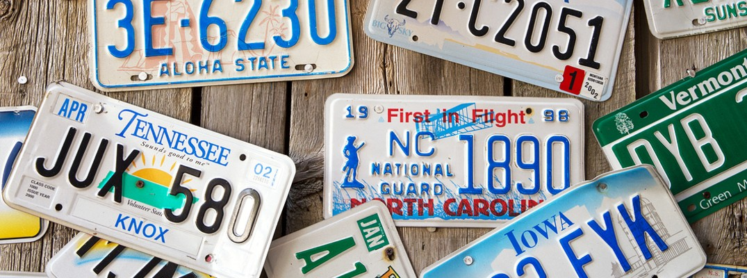 Group of license plates on wood background with Vermont plate shown in frame
