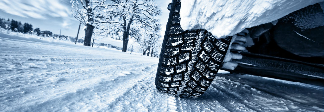 Close up of a car tire on a snowy road