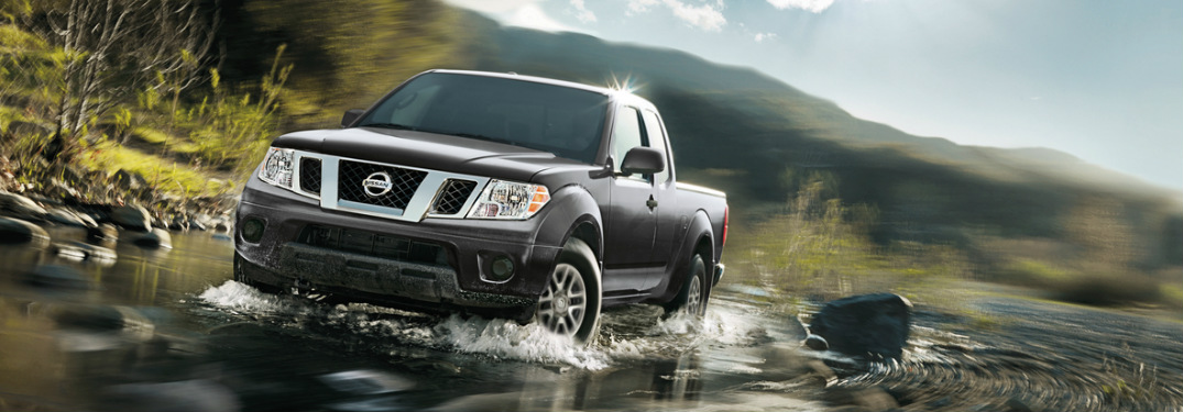 2018 Nissan Frontier in black driving through a small stream