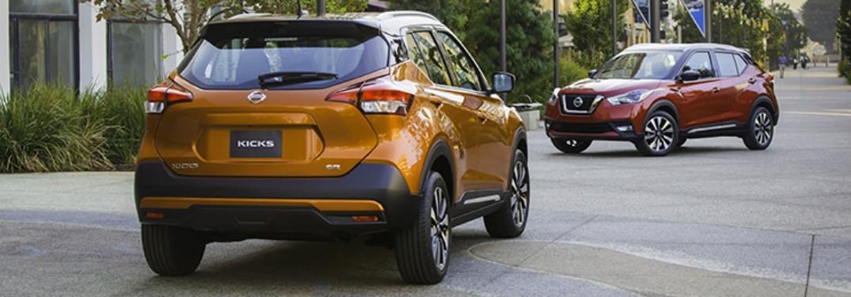 Two 2018 Nissan Kicks models parked on an empty concrete walkway