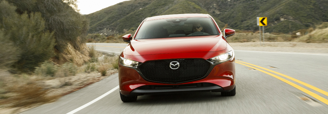 Red 2019 Mazda3 Hatchback driving on a mountainous highway