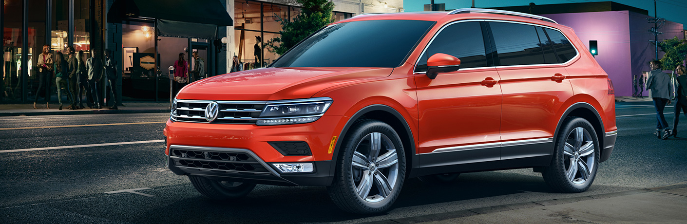 Exterior view of an orange 2018 Volkswagen Tiguan parked in the city at night