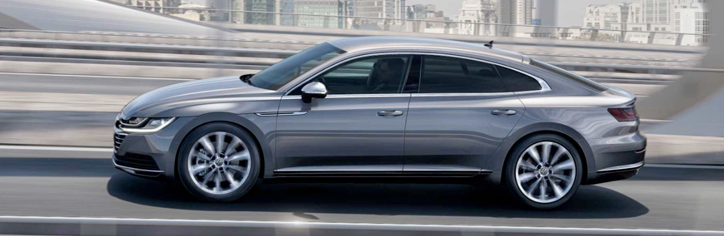 Exterior view of a silver 2019 Volkswagen Arteon driving down a city street